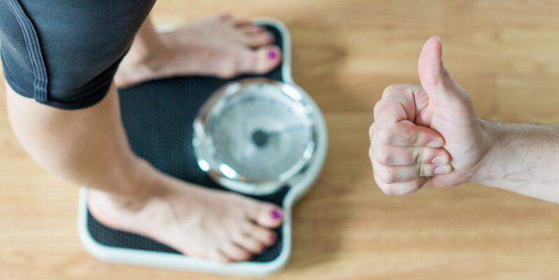 Mensch auf Waage mit persönlichen Trainer zur Präventation von Gewichtsproblemen